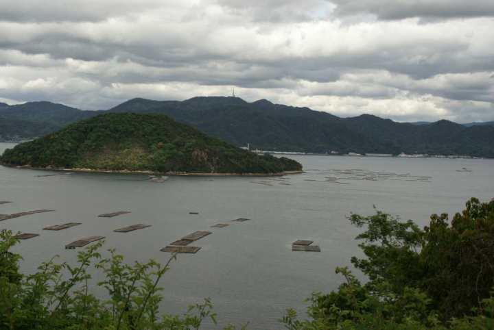 Vedere către est. Insula Taoshima (Toogeshima?)  În fundal, se poate vedea vîrful Egezan (cca. 600m) dintre tîrgurile Yano şi Saka, din plasa Aki.