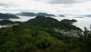 Vedere către sud. Se poate vedea aşezarea de la port, precum şi cele două promontorii de la extremitatea sudică. În planul terţ, insula Etajima, considerabil mai mare, mai dendritică şi mai populată.