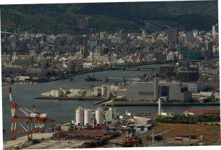În planul proxim se poate vedea terminalul de containere de pe grindul Ujina-Niho. În planul secund, pe grindul Yoshijima, o fabrică de ciment o instalaţie de prelucrare a gunoiului. Imediat în spatele ei, două antrepozite frigorifice. Pe braţ, mai în aval de pod, sunt pilonii noii căi ocolitoare a DN2. Cînd va fi gata, traficul de pe actualul DN2 e de aşteptat să scadă.